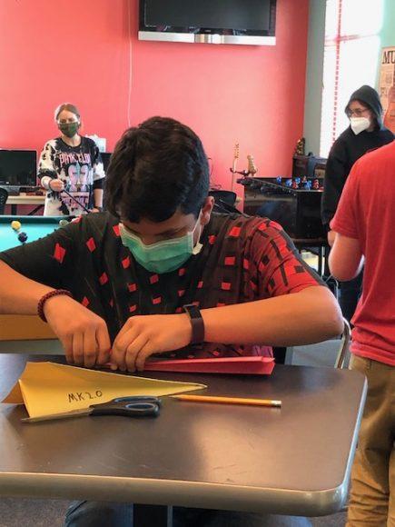 Teen making paper airplane